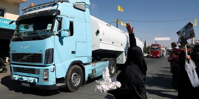 एक हिज़्बुल्लाह समर्थक ईरानी डीजल ले जाने वाले टैंकर ट्रकों के एक काफिले पर चावल फेंकता है जो सीरिया से लेबनान में सीमा पार करता है, पूर्वी शहर अल-ऐन, लेबनान, गुरुवार, 16 सितंबर, 2021 को पहुंचता है।