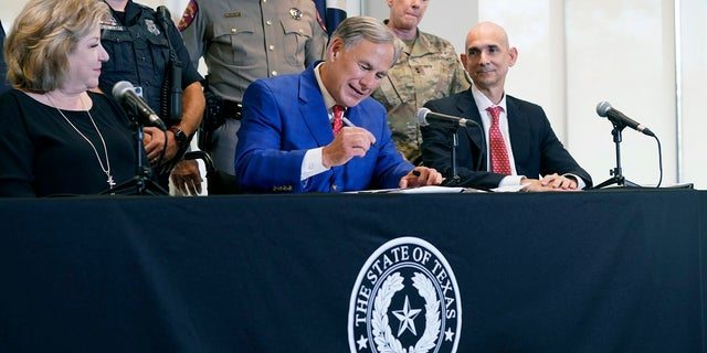 Texas Gov Greg Abbott, front center, is flanked by officials as he signs a bill that provides additional funding for security at the U.S.-Mexico border on Sept. 17. On Monday, he announced that Texas had obtained its own supply of monoclonal antibody treatments. (AP Photo/LM Otero)