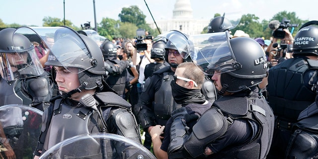 """Police circle a man, center with glasses, during a rally near the U.S. Capitol in Washington, Saturday, Sept. 18, 2021. The rally was planned by allies of former President Donald Trump and aimed at supporting the so-called """"political prisoners"""" of the Jan. 6 insurrection at the U.S. Capitol."""