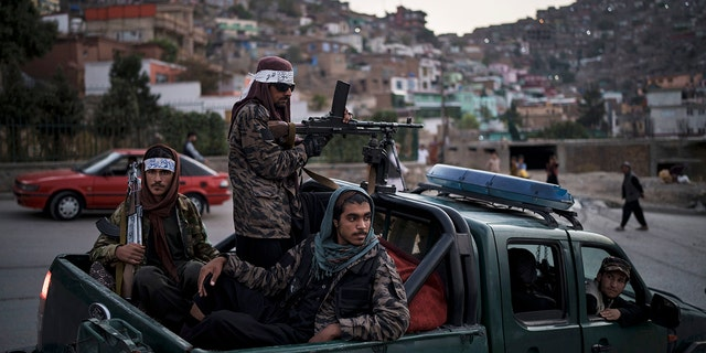 Taliban fighters sit on the back of a pickup truck as they stop on a hillside in Kabul, 아프가니스탄, 일요일, 씨족. 19, 2021. (AP Photo/Felipe Dana)