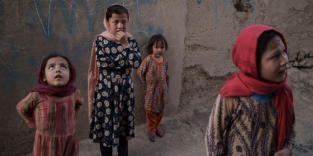 Afghan girls look up and listen as a neighbour describes when two men fell from a U.S. Air Force C-17 taking off from Kabul's International Airport on Aug. 16 and landed on the rooftop of his house in Kabul, 阿富汗, 星期五, 九月. 17, 2021. (AP Photo/Felipe Dana)
