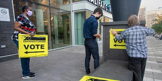 Les employés d'Élections Canada placent des affiches au Centre des congrès d'Halifax alors qu'ils se préparent pour l'ouverture des bureaux de vote lors de l'élection fédérale à Halifax le lundi 20 septembre 2021. (Andrew Vaughan/La Presse canadienne via AP)