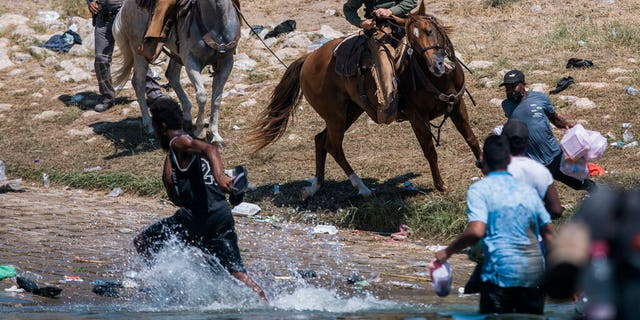 Sept. 19, 2021: U.S. Customs and Border Protection mounted officers attempt to contain migrants as they cross the Rio Grande from Ciudad Acuña, Mexico, into Del Rio, Texas. (AP Photo/Felix Marquez)