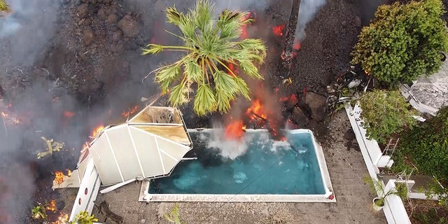 Hot lava reaches a swimming pool after an eruption of a volcano on the island of La Palma in the Canaries, Spain, Monday, Sept. 20, 2021.