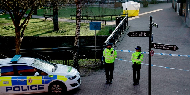 FILE - In this Wednesday, March 7, 2018 file photo, police officers guard a cordon around a police tent covering the the spot where former Russian double agent Sergei Skripal and his daughter were found critically ill.