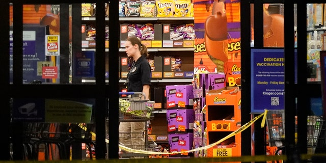 A responder walks down an aisle in a Kroger grocery store as the investigation goes into the night following a shooting earlier in the day on Thursday, Sept. 23, 2021, in Collierville, Tenn. (AP Photo/Mark Humphrey)