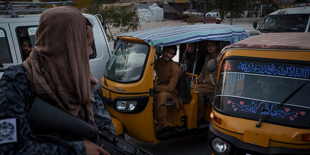 Afghan drivers and passengers stuck in a traffic jam look at Taliban fighters riding in the back of a vehicle in Kabul, Afghanistan, Monday, Sept. 20, 2021. (AP Photo/Felipe Dana)