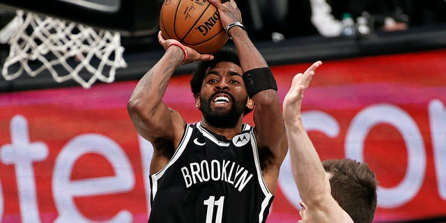 FILE - Brooklyn Nets guard Kyrie Irving (11) shoots against the Milwaukee Bucks during the second half of Game 1 of an NBA basketball second-round playoff series in New York, in this Saturday, June 5, 2021, file photo. Players like Kyrie Irving, who has refused to say if he will be vaccinated against COVID-19, will be subject to testing on all NBA practice, travel and game days this season. Fully vaccinated players will not. (AP Photo/Adam Hunger, File)