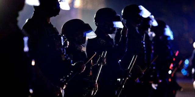 Dans cette photo d'archive du 3 novembre 2020, la police tient ses clubs alors qu'elle forme une ligne devant les partisans du président Donald Trump le jour des élections à Beverly Hills, en Californie. (Presse associée)