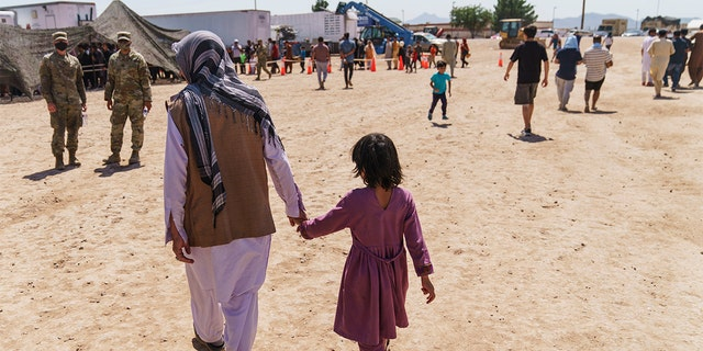 A man walks with a child through Fort Bliss' Doña Ana Village where Afghan refugees are being housed, in New Mexico. The Department of Homeland Security is not denying that hundreds Afghans being housed on U.S. military bases have left the installations. (AP Photo/David Goldman)