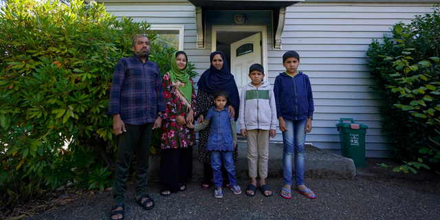 Abdul, left, who worked as a mechanic before he left Kabul, Afghanistan with his family about a month ago, poses for a photo, Thursday, Sept. 16, 2021, with his family in front of a rental house where they have been provided a place to stay in Seattle.