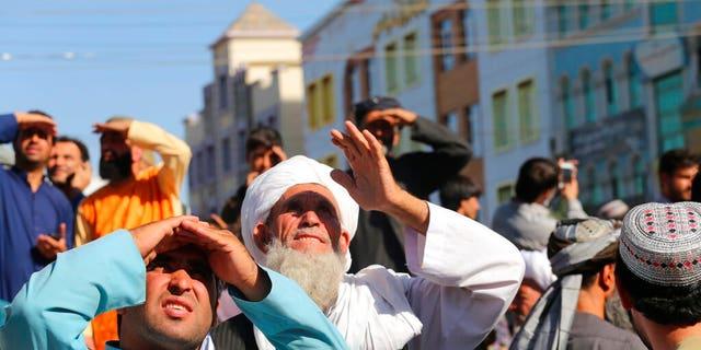 ĐÚNG NGÀY ĐẾN NGÀY 25 - Mọi người nhìn lên một xác chết bị Taliban treo cổ từ cần cẩu ở quảng trường chính của thành phố Herat, miền tây Afghanistan, vào thứ Bảy ngày 25 tháng 9 năm 2021. Một nhân chứng nói với hãng tin AP rằng thi thể của 4 người những người đàn ông được đưa đến quảng trường chính và ba người trong số họ được chuyển đến các khu vực khác của thành phố để trưng bày trước công chúng.  Taliban thông báo tại quảng trường rằng bốn người này đã bị bắt quả tang tham gia vào một vụ bắt cóc và bị cảnh sát giết chết.  (Ảnh AP)