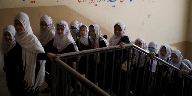 Girls walk upstairs as they enter a school before class in Kabul, Afghanistan, Sunday, Sept. 12, 2021.