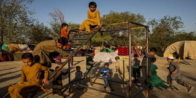 अफगान विस्थापित बच्चे सोमवार को अफगानिस्तान के काबुल में एक आंतरिक रूप से विस्थापित व्यक्तियों के शिविर में खेलते हैं।