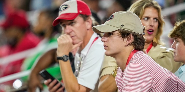 Sep 18, 2021; Athens, Georgia, USA; High school player Arch Manning looks on with his parents during a game between the South Carolina Gamecocks against the Georgia Bulldogs at Sanford Stadium.