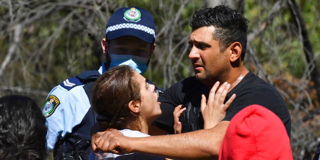 Anthony Elfalak, right, and his wife, Kelly, embrace after hearing their son AJ is found alive on the family property near Putty, north west of Sydney, Australia, Monday, Sept. 6, 2021.