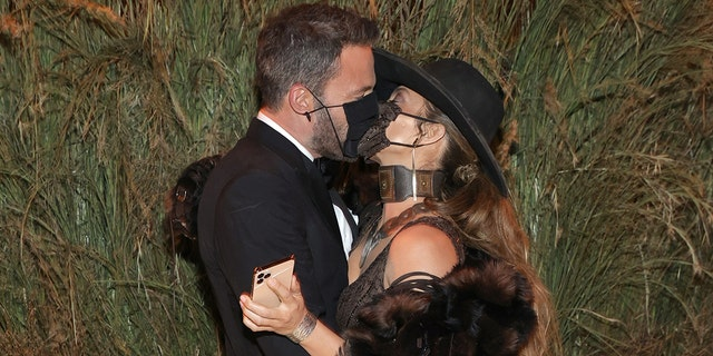Ben Affleck and Jennifer Lopez share a kiss through their masks at the the 2021 Met Gala.