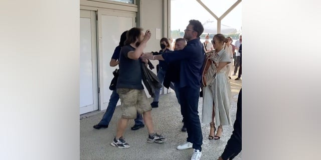 Ben Affleck held back a fan who tried to get a selfie with Jennifer Lopez before their bodyguard stepped in.