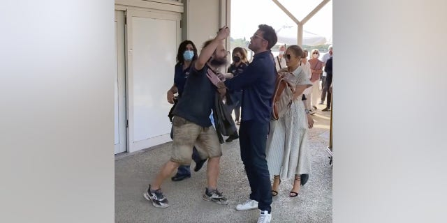Ben Affleck holds back a fan who tried to get a selfie with his girlfriend, Jennifer Lopez.