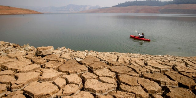 A kayaker fishes in Lake Oroville as water levels remain low due to continuing drought conditions in Oroville, Calif., Sunday, Aug. 22, 2021.