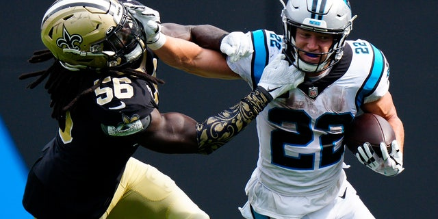Carolina Panthers running back Christian McCaffrey pushes away from New Orleans Saints outside linebacker Demario Davis during the second half of a game Sunday, Sept. 19, 2021, in Charlotte, N.C.