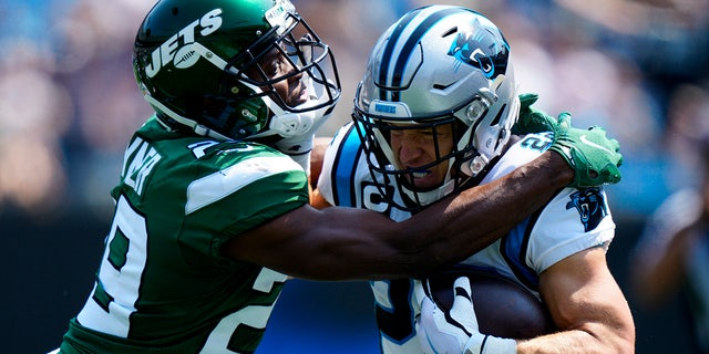 Carolina Panthers running back Christian McCaffrey is tackled by New York Jets free safety Lamarcus Joyner during the first half of a game Sept. 12, 2021, in Charlotte, N.C.