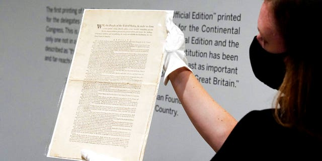 Ella Hall, a specialist in Books and Manuscripts at Sotheby's, in New York, holds a 1787 printed copy of the U.S. Constitution. (AP Photo/Richard Drew)