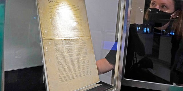 Ella Hall, a specialist in Books and Manuscripts, at Sotheby's, in New York, places a 1787 printed copy of the U.S. Constitution in its display case. It's the only copy that remains in private hands and has an estimate of $15 million-$20 million. (AP Photo/Richard Drew)