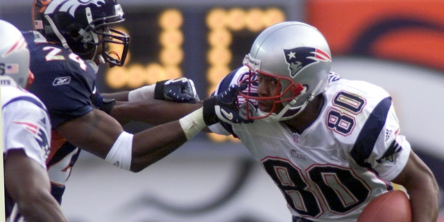 Denver Broncos cornerback Deltha O'Neal (L) grabs the face mask from New England Patriots wide receiver David Patten (80) in the first quarter in Denver on October 28, 2001.