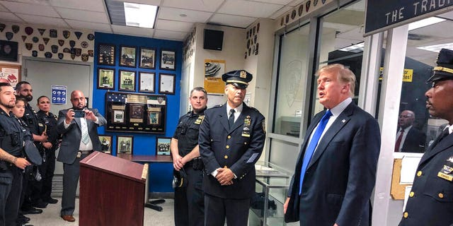 Former President Donald Trump, second from right, commemorated the 20th anniversary of the Sept. 11 attacks by visiting the NYPD's 17th police precinct in New York, on Saturday Sept. 11, 2021. (AP Photo/Jill Colvin)