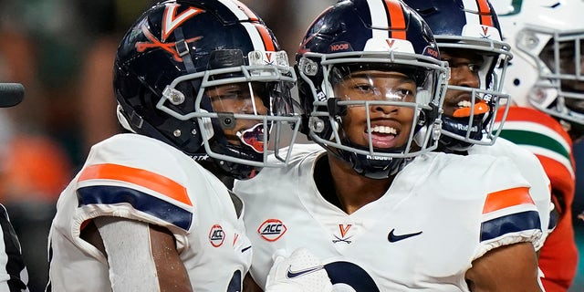 Virginia wide receiver Ra'Shaun Henry (2) congratulates wide receiver Dontayvion Wicks, after Wicks scored a touchdown during the second half of a NCAA college football game against Miami, Thursday, Sept. 30, 2021, in Miami Gardens, Fla.