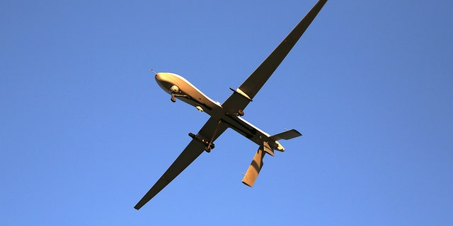 A U.S. Air Force MQ-1B Predator unmanned aerial vehicle (UAV), carrying a Hellfire missile flies over an air base after flying a mission in the Persian Gulf region.