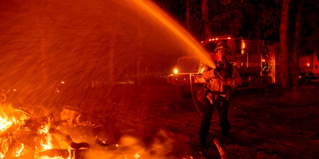 Firefighter Ron Burias battles the Fawn Fire as it spreads north of Redding, Calif. in Shasta County, di giovedì, Sett. 23, 2021.