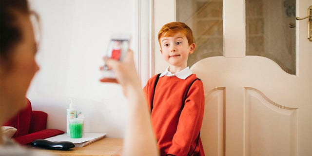 Little boy dressed for his first day back to school, having his photo taken by his Mother on her smartphone.
