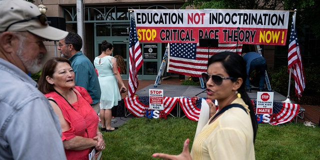 """People talk before the start of a rally against """"critical race theory"""" (CRT) being taught in schools at the Loudoun County Government center in Leesburg, Virginia on June 12, 2021. - """"Are you ready to take back our schools?"""" Republican activist Patti Menders shouted at a rally opposing anti-racism teaching that critics like her say trains white children to see themselves as """"oppressors."""" """"Yes!"""", answered in unison the hundreds of demonstrators gathered this weekend near Washington to fight against """"critical race theory,"""" the latest battleground of America's ongoing culture wars. The term """"critical race theory"""" defines a strand of thought that appeared in American law schools in the late 1970s and which looks at racism as a system, enabled by laws and institutions, rather than at the level of individual prejudices. But critics use it as a catch-all phrase that attacks teachers' efforts to confront dark episodes in American history, including slavery and segregation, as well as to tackle racist stereotypes. (Photo by ANDREW CABALLERO-REYNOLDS / AFP) (Photo by ANDREW CABALLERO-REYNOLDS/AFP via Getty Images)"""