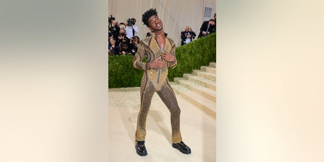 Lil Nas X in a black and gold bodysuit on the red carpet for the 2021 Met Gala in New York City.