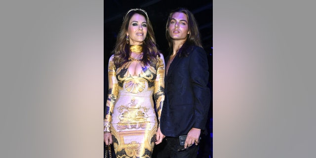 Damian Charles Hurley and Elizabeth Hurley are seen on the front row of the Versace special event during the Milan Fashion Week - Spring / Summer 2022 on September 26, 2021 in Milan, Italy.