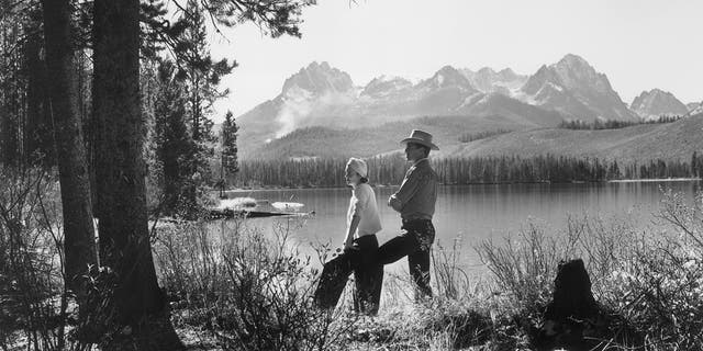 """American actor Gary Cooper and his wife """"Rocky"""" pose beside the Red Fish Lake in Idaho, circa 1940."""