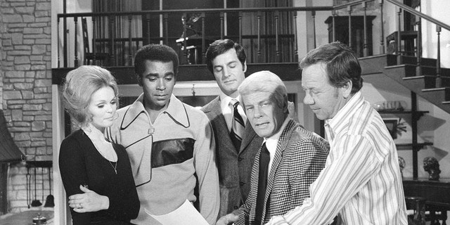 """""""Mission: Impossible"""" cast from left: Lynda Day George as Casey, Greg Morris as Barney Collier, Peter Lupus as Willy Armitage, Peter Graves as James Phelps and director Leslie H. Martinson in an off-camera moment during the episode """"Stone Pillow,"""" Oct. 20, 1971."""