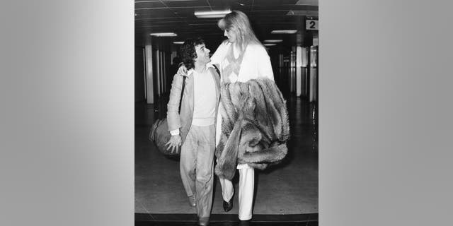 Comedian and actor Dudley Moore with his arm around then-girlfriend Susan Anton, arriving at Heathrow Airport, London, October 1st 1980.