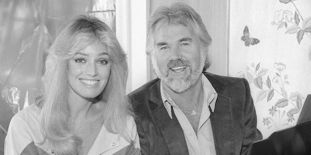American actress and singer Susan Anton American singer, songwriter, musician, actor, record producer, and entrepreneur Kenny Rogers (1938-2020) pose for a portrait circa 1987 in Los Angeles, California.