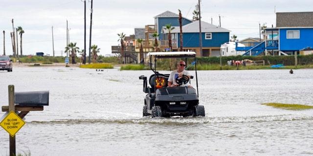 Joe Ward drives down through floodwaters from Hurricane Nicholas Tuesday, Sept. 14, 2021, in Surfside Beach, Texas.