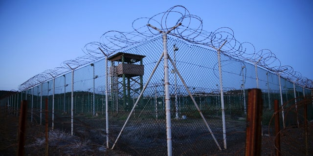 Chain link fence and concertina wire surround a deserted guard tower within Joint Task Force Guantanamo's Camp Delta at the U.S. Naval Base in Guantanamo Bay, Cuba, in 2016.