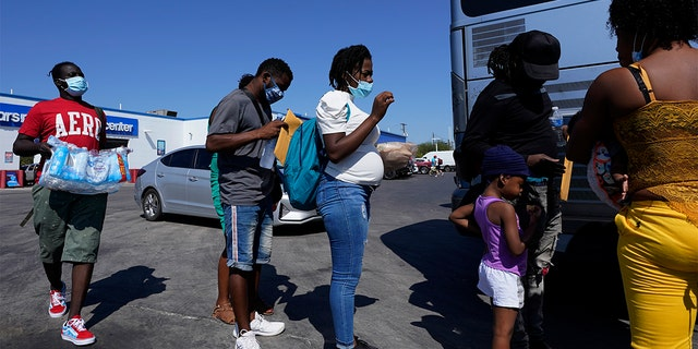 In this Sept. 20, 2021, file photo, migrants, many from Haiti, board a bus after they were processed and released after spending time at a makeshift camp near the International Bridge in Del Rio, Texas. (AP Photo/Eric Gay, File)