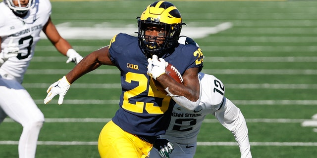 Michigan Wolverines running back Hassan Haskins rushes against the Michigan State Spartans at Michigan Stadium.