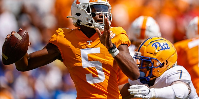 Tennessee quarterback Hendon Hooker (5) throws to receiver as he's hit by Pittsburgh linebacker SirVocea Dennis (7) during the first half of an NCAA college football game Saturday, 九月. 11, 2021, 在诺克斯维尔, 天恩. (AP Photo/Wade Payne)