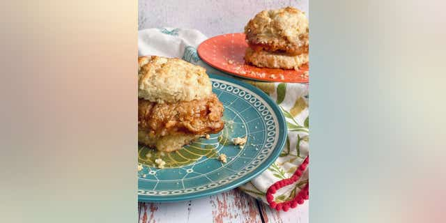 Each buttermilk biscuit slice can receive a dollop of fresh honey butter before the chicken is placed in between.