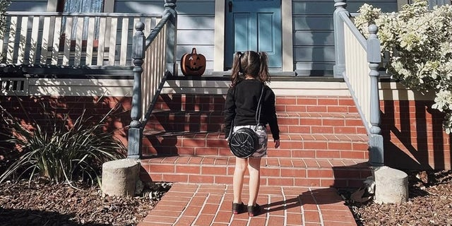 """Aria Alvarado is seen in front of the character Michael Myers' house from the movie, """"Halloween."""""""