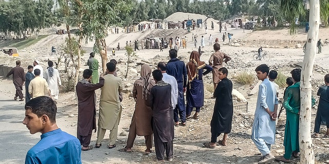 Taliban members and people gather at the site of a bomb explosion which targeted a pickup truck carrying Taliban fighters in Jalalabad on September 19, 2021, a day after at least two people were killed in a series of blasts in the area.