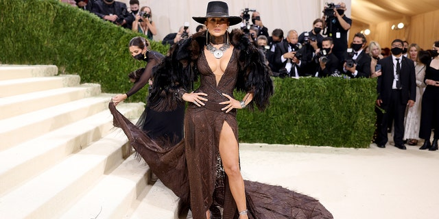 Jennifer Lopez goes with the cowboy hat and Western look in a flowing brown gown with a high-thigh slit and an elegant train.